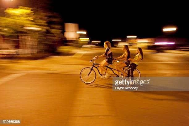 Kids ride a tandem bike at night on Main Street in the tiny Lake Superior town of Grand Marais, Minnesota