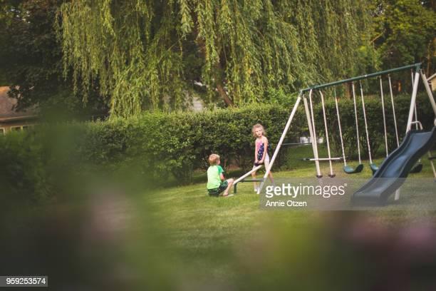 kids riding a small teeter totter - movimiento hacia abajo fotografías e imágenes de stock