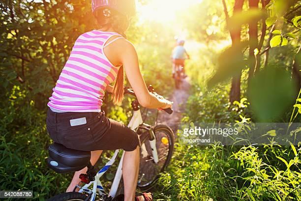 Kinder Reiten Fahrräder auf Pfad wunderschönen wald