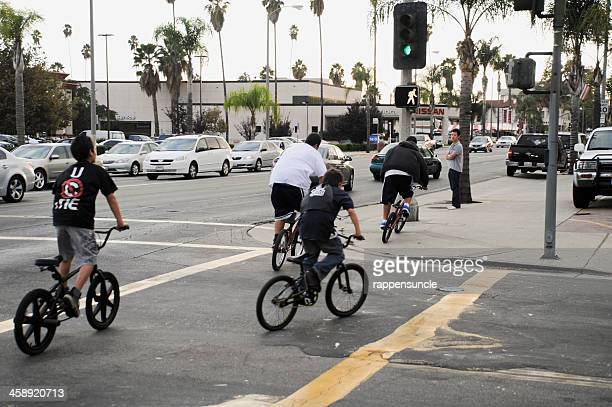 kids riding bikes on the street - alhambra city of los angeles stock photos and pictures