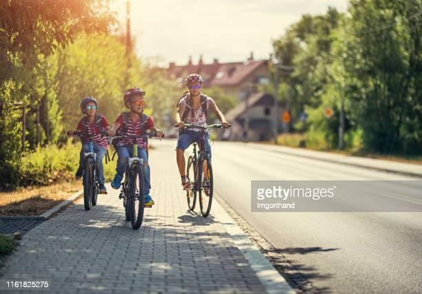 kinder mit dem fahrrad zur schule - gehweg stock-fotos und bilder