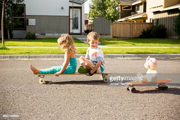 Kids riding on skateboard outside.
