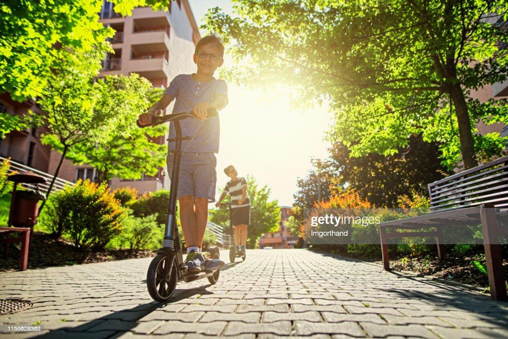 Kinderen rijden scooters in de stad woonwijk. : Stockfoto