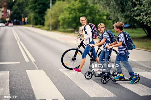 gosses conduisant à l'école sur le vélo et les scooters - sûreté photos et images de collection