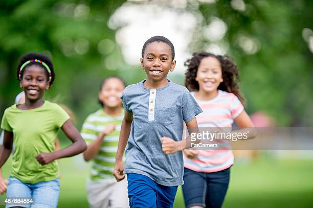 kids runnign around at the park - tag game stock photos and pictures