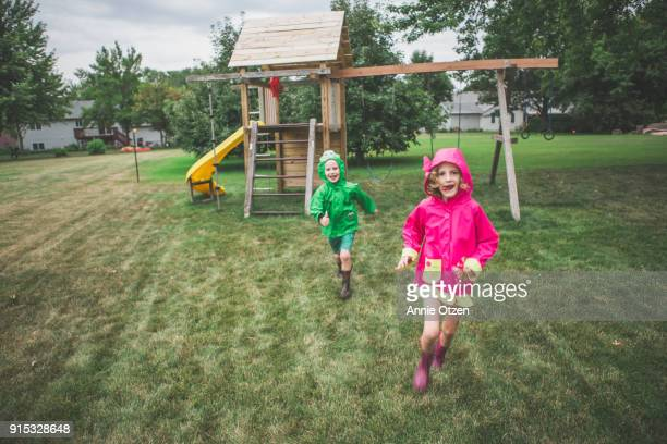 Kids running across a backyard in raincoats
