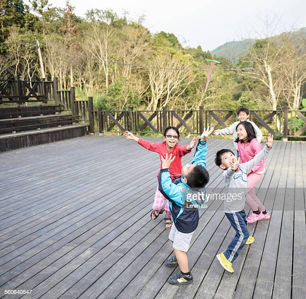 Kids running and playing on wooden patio