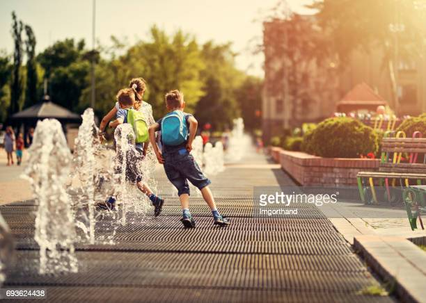 kids running between fountains on a hot summer day. - public park stock photos and pictures