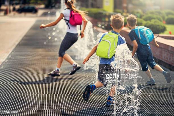 kids running between fountains on a way from school - fountain stock pictures, royalty-free photos & images
