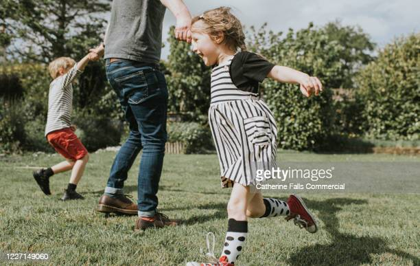 kids running in a garden - spinning stock pictures, royalty-free photos & images