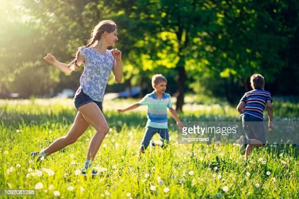 タンポポの草原を走りましたが - 鬼ごっこ ストックフォトと画像