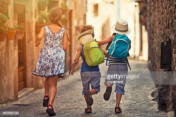 Enfants courir dans la rue méditerranéenne.