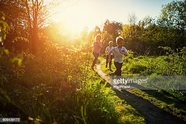 kids running in nature. - sunlight stock pictures, royalty-free photos & images