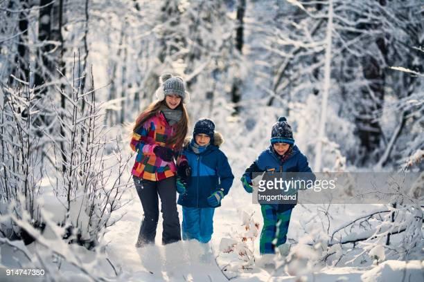 Kids running in winter forest