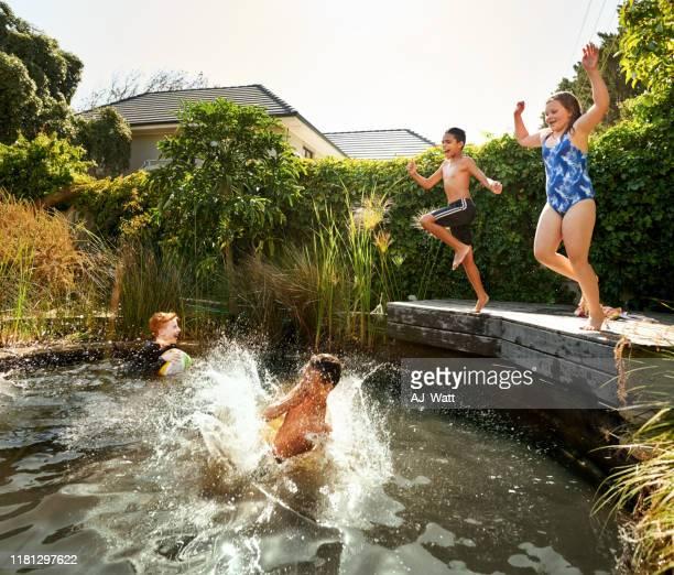 niños corriendo a la piscina - charca fotografías e imágenes de stock