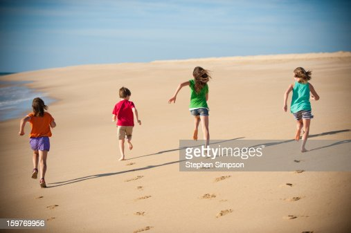 Girls Running On Pristine Empty Beach Stock Photo