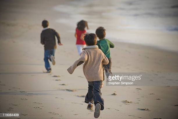 kids running on the beach in the Fall