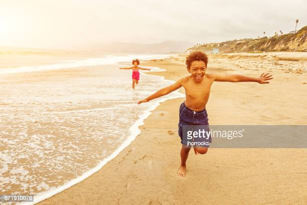 kids running on the beach - la beach stock pictures, royalty-free photos & images