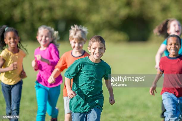 kids running outside for gym class - tag game stock photos and pictures