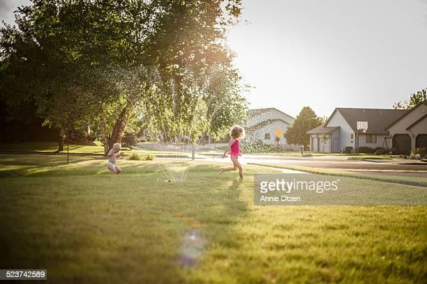 kids running through sprinkler - diaper kids stock pictures, royalty-free photos & images