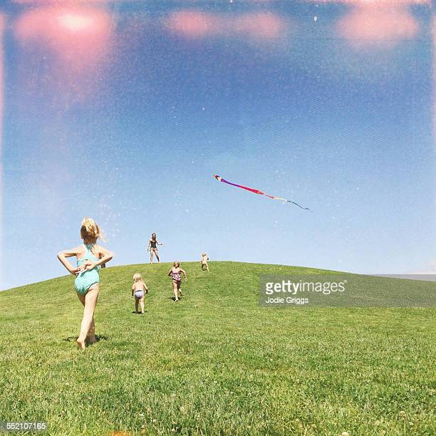 Kids running to the top of a hill to fly a kite