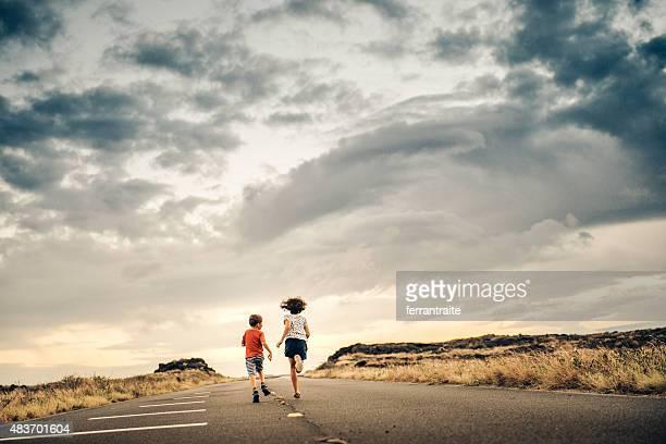 Enfants courir en direction du coucher de soleil sur une route vide