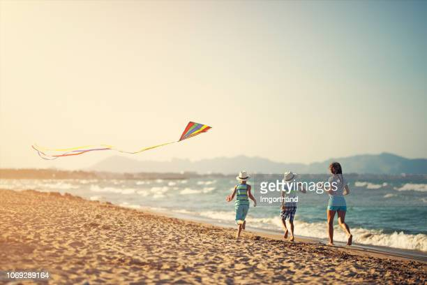 kids running with kite on a beach - kite toy stock pictures, royalty-free photos & images