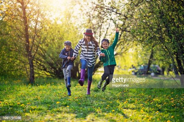 kids running with spring joy - springtime stock pictures, royalty-free photos & images