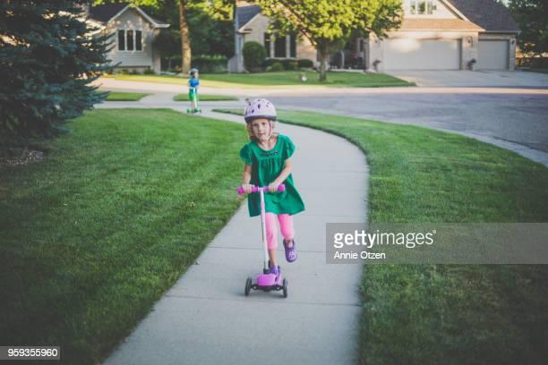 Kids scooting down a sidewalk