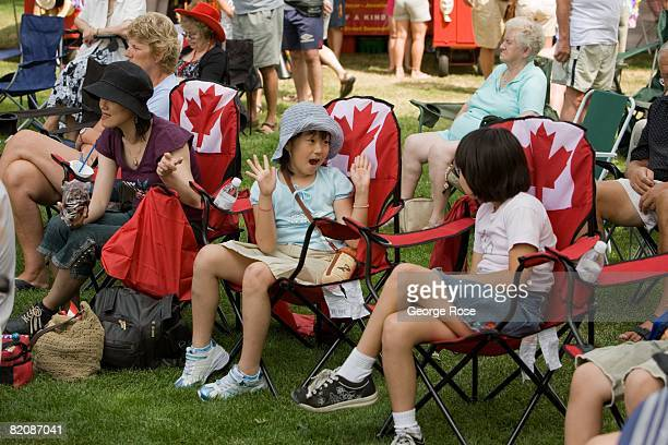 Kids seated in Canadian maple leaf flag chairs wait for the Canada Day festivities to begin in this 2008 Penticton British Columbia Canada summer...