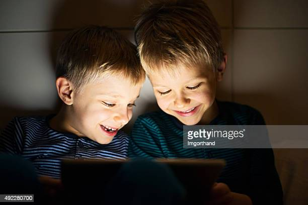 Kids secretly playing with digital tablet at night