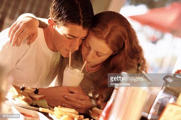 Kids sharing a milkshake