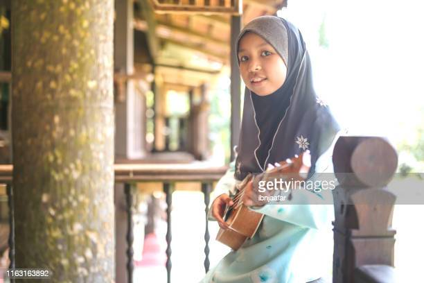 kids singing and playing with guitar in house - ibnjaafar stock photos and pictures