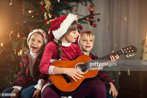 Kids singing carols near the christmas tree