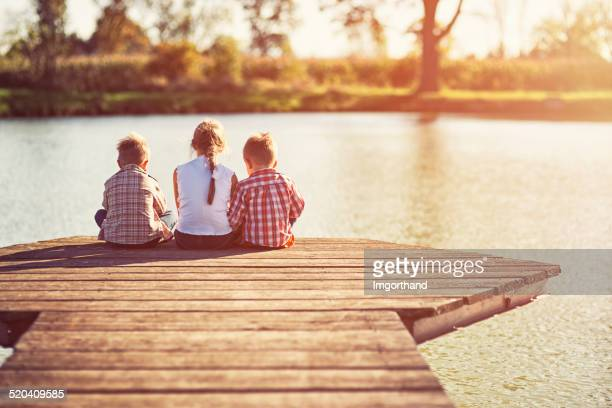 kids sitting at the pier. - jetty stock pictures, royalty-free photos & images