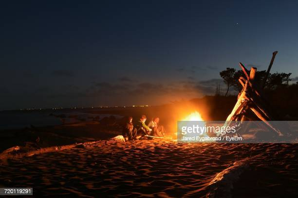 Kids Sitting By Bonfire At Beach Against Sky During Night