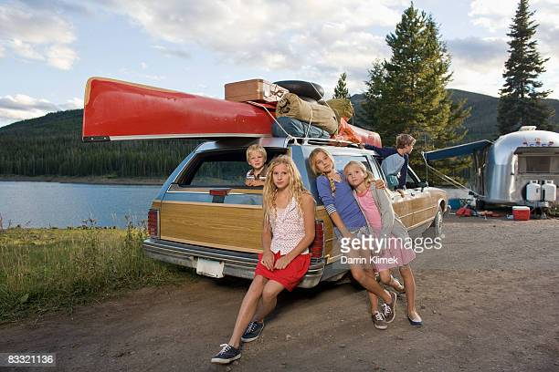 Kids sitting by car on family road trip