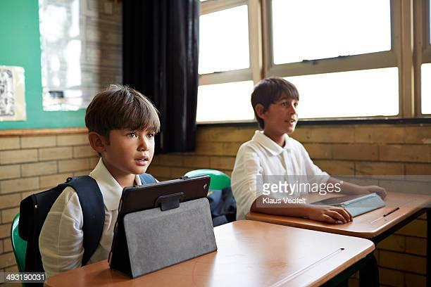 Kids sitting by desks in school