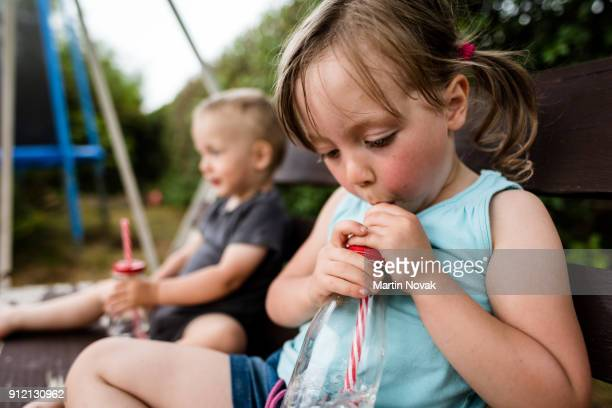 Kids sitting on backyard bench and sipping water