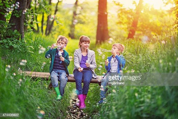 Kids sitting on little bridge and blowing bubbles