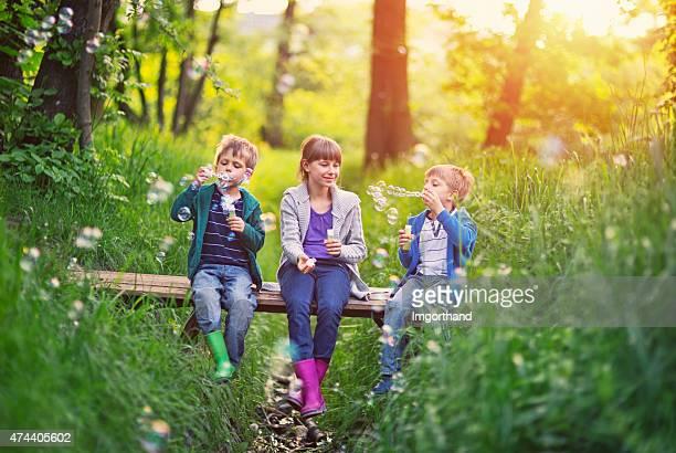 Kinder sitzen auf der kleinen Brücke und Blasen Blasen