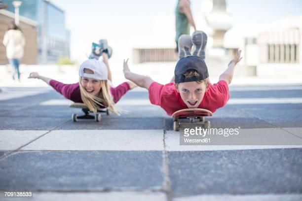 Kids skateboarding in the street, lying on belly