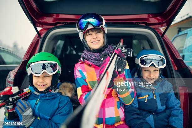 esquiadores de crianças sentado na mala do carro - ski holiday - fotografias e filmes do acervo