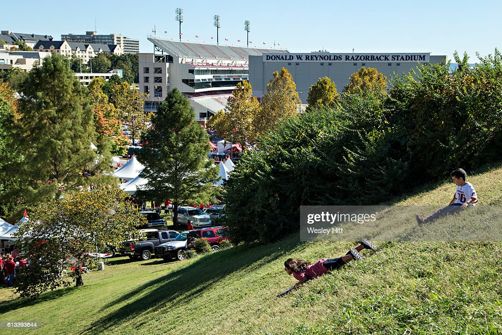 Kids slide down a grassy hill in view of the stadium before a game between the Arkansas Razorbacks and the Alabama Crimson Tide at Razorback Stadium on October 8, 2016 in Fayetteville, Arkansas.