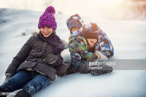 Kids sliding down the hill in winter