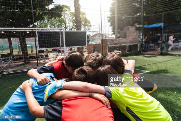 kids soccer team huddling together - football team stock pictures, royalty-free photos & images
