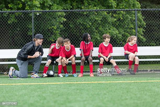 kids soccer team interacting with coach on the bench - club football stock pictures, royalty-free photos & images