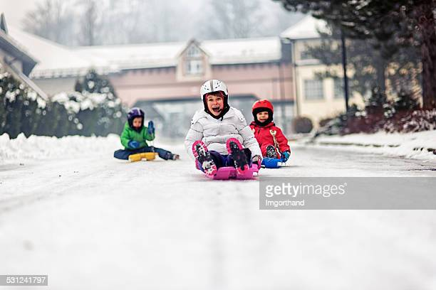 kids speed sledge race - funny snow stock photos and pictures