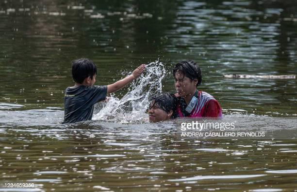 Kids splash in the river as they cool off during a heat wave, on the Rappahannock river in Fredricksburg, Virginia on August 13, 2021. - July was the...