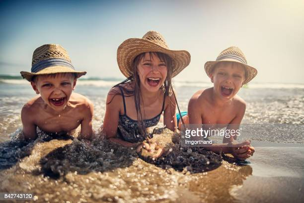kids splashing in the mediterranean sea - hat stock pictures, royalty-free photos & images